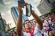 01 MARCH 2013 - BANGKOK, THAILAND: .A Pheu Thai supporter tries to photograph the stage at the last Pheu Thai campaign rally for the Bangkok Governor's election. The election is Sunday, March 3 and no campaigning is allowed 24 hours before election day. Police General Pongsapat Pongcharoen (retired), a former deputy national police chief who also served as secretary-general of the Narcotics Control Board is the Pheu Thai Party candidate in the upcoming Bangkok governor's election. He resigned from the police force to run for Governor. Former Prime Minister Thaksin Shinawatra reportedly personally recruited Pongsapat. Most of Thailand's reputable polls have reported that Pongsapat is leading in the race and likely to defeat Sukhumbhand Paribatra, the Thai Democrats' candidate and incumbent. The loss of Bangkok would be a serious blow to the Democrats, whose national base has been the Bangkok area.    PHOTO BY JACK KURTZ