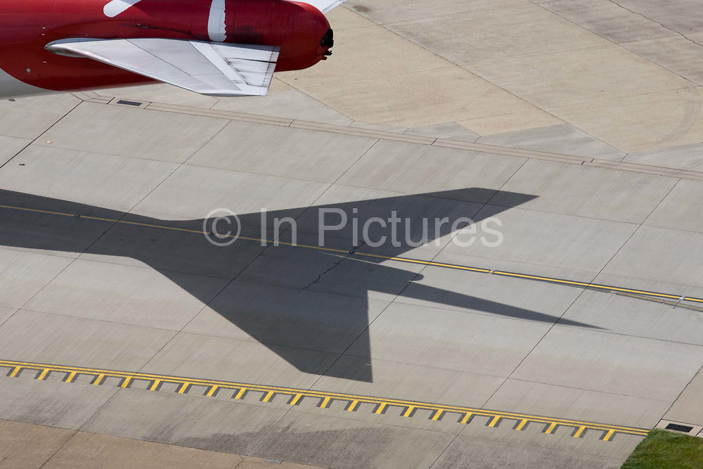Aerial view (from control tower) of Virgin Atlantic airliner's wing and engine at London Heathrow airport. Taxiing along the centreline that helps pilots navigate to specific locations around the airport consisting of five terminals on a site that covers 12.14 square kilometres (4.69 sq mi). London Heathrow is a major international airport, the busiest airport in the United Kingdom and the busiest airport in Europe by passenger traffic. It is also the third busiest airport in the world by total passenger traffic, handling more international passengers than any other airport around the globe.