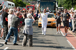 The Olympic Torch relay reaches Sheffield on day 38 coverage from the Chapeltown - Ecclesfield - Parson Cross section of the Journey.<br /> Christopher Godwin Torch Bearer 103 carries the torch out of Chapeltown and on up Ecclesfield Road<br /> 25 June 2012.Image © Paul David Drabble