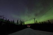 The Alaska Railroad runs along a snow-covered dirt road as the Aurora rises overhead