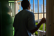 A prisoner looks out at the blue sky though a gated doorway to one of the industrial units inside HMP/YOI Portland, a resettlement prison with a capacity for 530 prisoners. Dorset, United Kingdom.