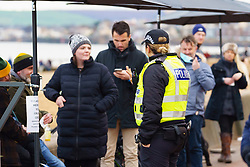 Portobello, Scotland, UK. 10 January 2020. Despite a national lockdown currently enforced in Scotland, Portobello promenade and beach was busy with large numbers of people spending Sunday afternoon there. Several police patrols were evident mostly keeping low key but officers spoke to cafe owners to urge them to keep correct social distancing between customers. Pic; Police speak to cafe customers to explain social distancing requirements.  Iain Masterton/Alamy Live News