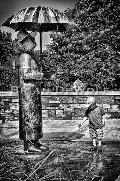 Drops of water falling from the Rain Man statue's umbrella fascinate a little boy.  Aspect Ratio 1w x 1.5h.