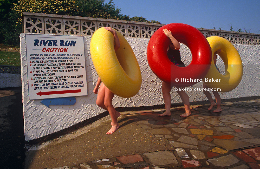Awkwardly, carrying their giant rubber rings by wrapping their left hands over the top curves, three kids make their way tentatively down a ramp of concrete to a poolside ride called River Run.