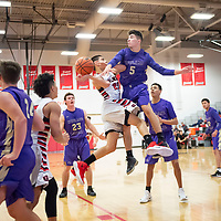 Nicolas Trujillo (21), near the baseline, is fouled hard by Ty Jenks (5) of Kirtland Central as he drives to the basket at the Eddie Pena Classic in Grants on Friday. Grants won 60-42.