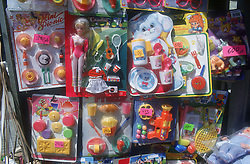 Various packets of plastic dolls and toys displayed outside toyshop,