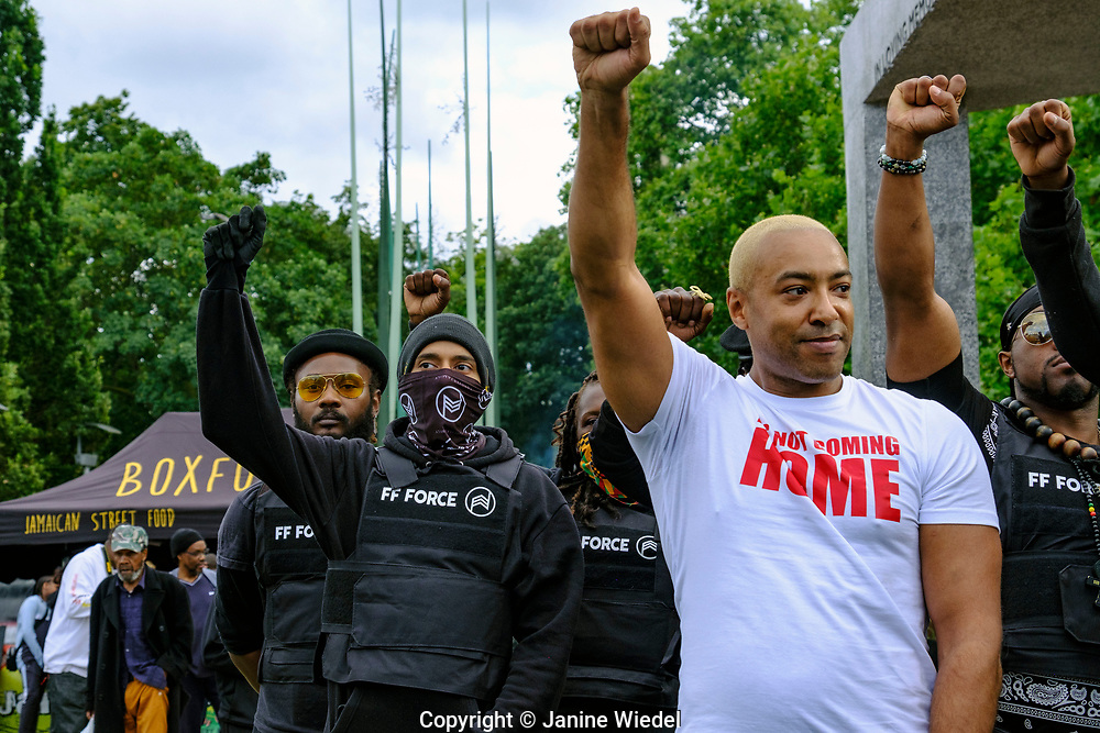 """Musician Koba Kane with black rights group FF Force ( Forever Family Force ) at  Reparations Rebellion event on Emancipation Day in Windrush Square Brixton 2021. Koba performing his latest song """"It's not coming Home""""."""