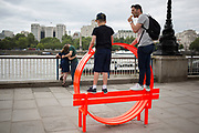 For the Summer season, brightly coloured odd shaped benches are set up along the riverside walkway where people interact with them on the Southbank, London, United Kingdom. The South Bank is a significant arts and entertainment district, and home to an endless list of activities for Londoners, visitors and tourists alike. (photo by Mike Kemp/In Pictures via Getty Images)