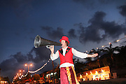 Clown on stilts with a megaphone at a festival. Photographed in Israel at Kfar Yona