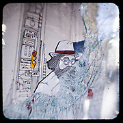 Shattered glass on a shop front on Panepistimiou Street.<br /> <br /> Following the murder of a 15 year old boy, Alexandros Grigoropoulos, by a policeman on 6 December 2008 widespread riots, protests and unrest followed lasting for several weeks and spreading beyond the capital and even overseas<br /> <br /> When I walked in the streets of my town the day after the riots I instantly forgot the image I had about Athens, that of a bustling, peaceful, energetic metropolis and in my mind came the old photographs from WWII, the civil war and the students uprising against the dictatorship. <br /> <br /> Thus I decided not to turn my digital camera straight to the destroyed buildings but to photograph through an old camera that worked as a filter, a barrier between me and the city.