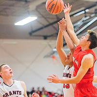 Grants Pirate Samuel Sanchez (33), right and  Academy Charger Elijah Lucero (10) reach for a rebound in Grants Tuesday.