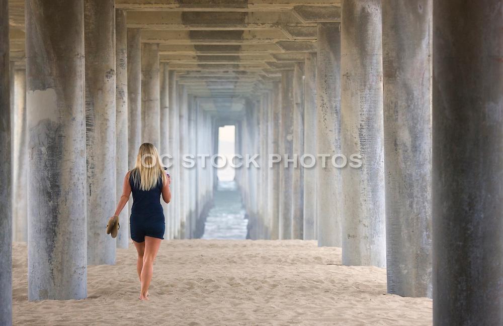 Woman Walking Under The Huntington Beach Pier Orange County, California