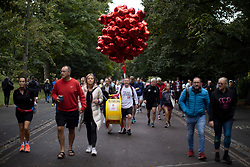 © Licensed to London News Pictures. 03/10/2021. London, UK. A runners with a large quantity of heart shaped balloons arrives in Greenwich Park ahead of the start of the London Marathon.This London Marathon will be the first full scale staging of the race in more than two years due to the Coronavirus Pandemic.  Photo credit: George Cracknell Wright/LNP