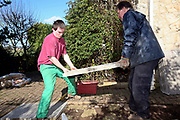 Ben, a young offender laying down paving stones with Geoff, the course instructor for the Inside Out Trust project, Wetherby Young Offenders Secure College of Learning. Yorkshire, UK. It is part of Ben's education to perform manual tasks for local elderly residents in the community. HMP / YOI College of Secure Learning Wetherby is a male juveniles prison, located in Wetherby, West Yorkshire, England. The prison is operated by Her Majesty's Prison Service.