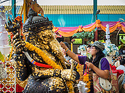 20 SEPTEMBER 2015 - SARIKA, NAKHON NAYOK, THAILAND:  People make merit by rubbing gold leaf on a statue of Ganesha at the Ganesh festival at Shri Utthayan Ganesha Temple in Sarika, Nakhon Nayok. Ganesh Chaturthi, also known as Vinayaka Chaturthi, is a Hindu festival dedicated to Lord Ganesh. Ganesh is the patron of arts and sciences, the deity of intellect and wisdom -- identified by his elephant head. The holiday is celebrated for 10 days. Wat Utthaya Ganesh in Nakhon Nayok province, is a Buddhist temple that venerates Ganesh, who is popular with Thai Buddhists. The temple draws both Buddhists and Hindus and celebrates the Ganesh holiday a week ahead of most other places.   PHOTO BY JACK KURTZ