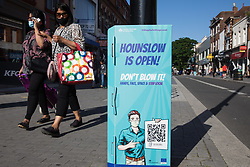 London, UK. 17th July, 2021. Members of the public pass a London Borough of Hounslow Covid-19 public information sign urging residents to take precautions to minimise the spread of the coronavirus amid rising concern regarding the Delta variant. The UK government is currently still expected to lift almost all restrictions on social contact on 19th July, known as 'Freedom Day', but the current wave driven by the Delta variant is not expected to peak until mid-August.