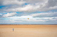 Scenic landscape of the wide beach sands at Holkham in north Norfolk, England. With young child flying a kite.
