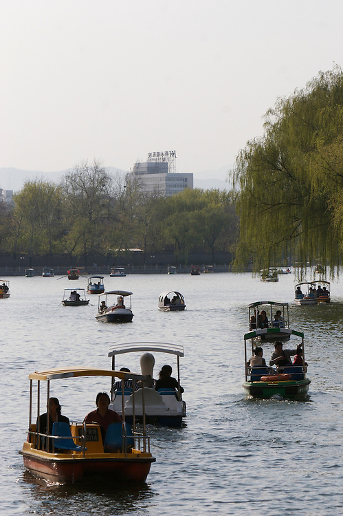 Visitors enjoy Houhai lake with rentals paddle boats.  Houhai is one of the three lakes in the Shichahai area in Beijing,China.