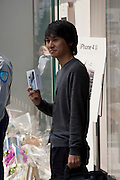 Yosuke Ishinabe, froim Saitama, who started queueing on Tuesday, and was first in line at the Apple store exits the store with his brand new iphone4S in Ginza, Tokyo, Japan. Friday October 14th 2011. The latest version of the popular iphone was released worldwide on October 14th. Japans flagship Apple store in Ginza was opened at 8am for the 800 people that had been waiting to be the first to purchase the new telephone.