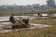 A farmer prepares rice fields for planting in  Ha Tay Province, outside Hanoi, Vietnam.