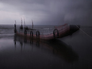 Dream-like image of a wooden barge moored on a beach in Mong Cai, Quang Ninh Province, Northern Vietnam, Southeast Asia