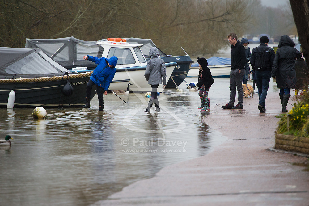 Children play on a flooded riverside road in Henley On Thames, Oxfordshire as heavy rains in the River Thames catchment area and saturated ground causes the river to rise to within inches of bursting its banks.. April 02 2018.