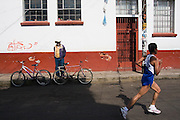 A man watches a participant of the half-marathon running through Paracho, Michoacan state, Mexico on August 9, 2008 during the annual Feria Internacional de la Guitarra.