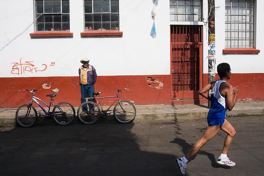A man watches a participant of the half-marathon running through Paracho, Michoacan state, Mexico on August 9, 2008 during the annual Feria Internacional de la Guitarra.
