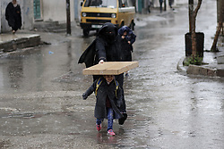 November 10, 2018 - Gaza, Palestine - Mother seen protecting her child from rain in the centre of Gaza City. (Credit Image: © Mohamed Zarandah/SOPA Images via ZUMA Wire)