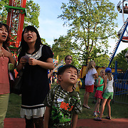 A family watch the rides during the May Fair at Saint Mark's Church, New Canaan, Connecticut, USA. 12th May 2012. Photo Tim Clayton