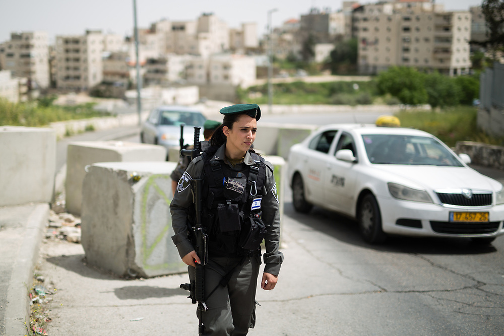 Israeli Border Police Women Corporal Mor Hadad (L) and  Staff Sergeant Chen Cohen (behind) stand guard at the exit of the East Jerusalem neighborhood of Issawiya, in Jerusalem, Israel, on April 10, 2016.