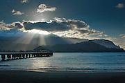 Rays of light radiate over the wharf at Hanalei Bay, Kauai, Hawaii