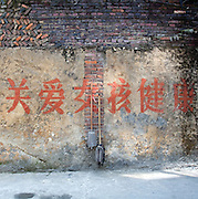 Chinese characters painted on a wall encourage parents to love their daughters in the town of Longyan in Fujian Province. The area is still very traditional and many couples are disappointed when they give birth to female children.