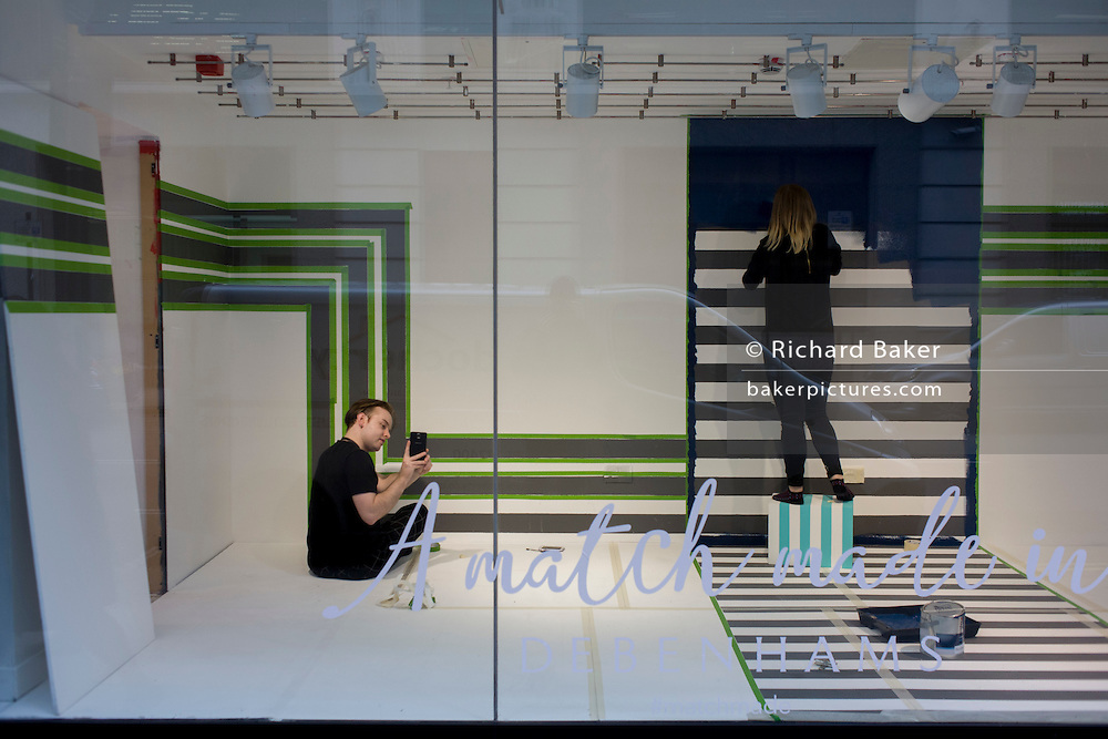 Window dressers prepare a new window design with a stripes theme in the Oxford Street branch of retailer Debenhams.