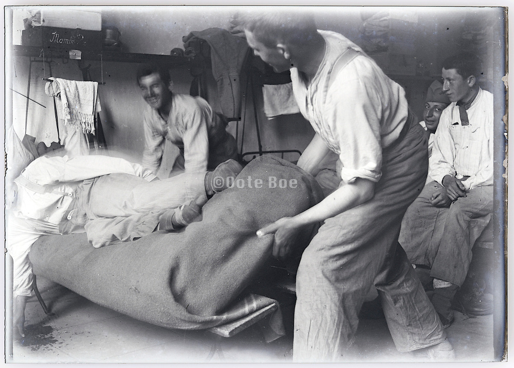 young men having fun by throwing person from his bed early 1900s