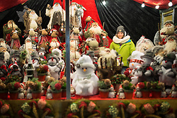© Licensed to London News Pictures . Manchester , UK . A stall holder with reindeer , snowmen and other festive dolls . FILE PHOTO DATED 20/11/2013 of Christmas Markets in Manchester as temperatures drop and 2014 seasonal markets start up across the country , selling mulled wine , german hot dogs , dutch pancakes , wooly hats and many other festive frivolities . Christmas markets provide an economic boost to many city centres and create a festive atmosphere on otherwise cold and dark nights . . Photo credit : Joel Goodman/LNP