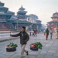 A man carries vegetable to sell thorugh Durbar Square in Kathmandu, Nepal, 1986.