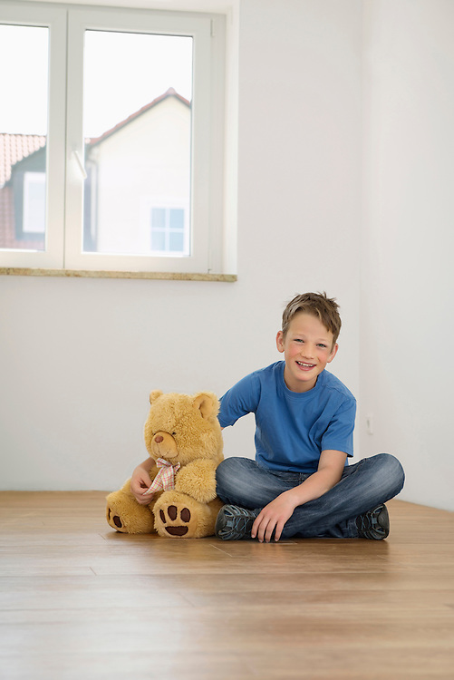 Young boy alone empty room teddy moving home