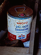 Rusting, leaking five gallon container of DDT among discarded items in an abandoned barn, Clarkston, Michigan.