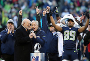 (L-R) Players and team executives hold their hands and fingers in the air as sports analyst and former Pittsburgh Steelers quarterback Terry Bradshaw congratulates Seattle Seahawks head coach Pete Carroll after the Seahawks win the NFL week 20 NFC Championship football game against the Green Bay Packers on Sunday, Jan. 18, 2015 in Seattle. The Seahawks won the game 28-22 in overtime. ©Paul Anthony Spinelli