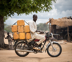 30 May 2019, Mokolo, Cameroon: A man rides a motorbike loaded with jerry cans for water, through the Minawao camp for Nigerian refugees. The Minawao camp for Nigerian refugees, located in the Far North region of Cameroon, hosts some 58,000 refugees from North East Nigeria. The refugees are supported by the Lutheran World Federation, together with a range of partners.