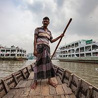A ferryman navigates the Buriganga river, Dhaka, Bangladesh