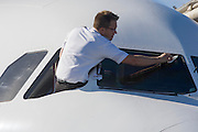 An anonymous airline pilot leans out of his cockpit window to clean marks off of the airliner's windscreen.