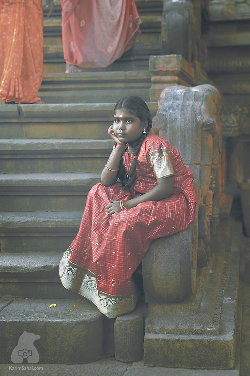 A girl with a red saree sits on the stairs of a temple in Thanjavur, Tamil Nadu, India
