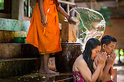 "02 JULY 2013 - ANGKOR WAT, SIEM REAP, SIEM REAP, CAMBODIA:  A Buddhist monk blesses a couple by splashing water on them at a small monastery near the Bayon temple in the Angkor Wat complex. Angkor Wat is the largest temple complex in the world. The temple was built by the Khmer King Suryavarman II in the early 12th century in Yasodharapura (present-day Angkor), the capital of the Khmer Empire, as his state temple and eventual mausoleum. Angkor Wat was dedicated to Vishnu. It is the best-preserved temple at the site, and has remained a religious centre since its foundation – first Hindu, then Buddhist. The temple is at the top of the high classical style of Khmer architecture. It is a symbol of Cambodia, appearing on the national flag, and it is the country's prime attraction for visitors. The temple is admired for the architecture, the extensive bas-reliefs, and for the numerous devatas adorning its walls. The modern name, Angkor Wat, means ""Temple City"" or ""City of Temples"" in Khmer; Angkor, meaning ""city"" or ""capital city"", is a vernacular form of the word nokor, which comes from the Sanskrit word nagara. Wat is the Khmer word for ""temple grounds"", derived from the Pali word ""vatta."" Prior to this time the temple was known as Preah Pisnulok, after the posthumous title of its founder. It is also the name of complex of temples, which includes Bayon and Preah Khan, in the vicinity. It is by far the most visited tourist attraction in Cambodia. More than half of all tourists to Cambodia visit Angkor.         PHOTO BY JACK KURTZ"
