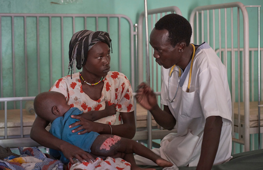 Nurse Lakuwa Lokolo Rama talks with a mother and child in the pediatric ward of the Mother of Mercy Hospital in Gidel, a village in the Nuba Mountains of Sudan. The area is controlled by the Sudan People's Liberation Movement-North, and frequently attacked by the military of Sudan. The Catholic hospital is the only referral hospital in the war-torn area.<br /> <br /> Rama is a 2016 graduate of the Catholic Health Training Institute, a school in Wau, South Sudan, sponsored by Solidarity with South Sudan.