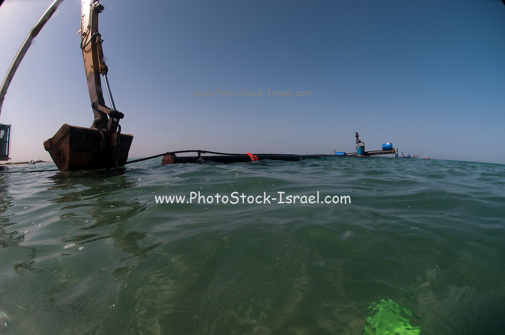 Workers laying a brine discharge pipe from a desalination plant on the seabed to a distance of 300 meter from the shore. The pipe is drawn out to sea as a whole unit. Brine discharge can have a negative impact on the ocean ecosystem. Photographed in Israel Mediterranean sea