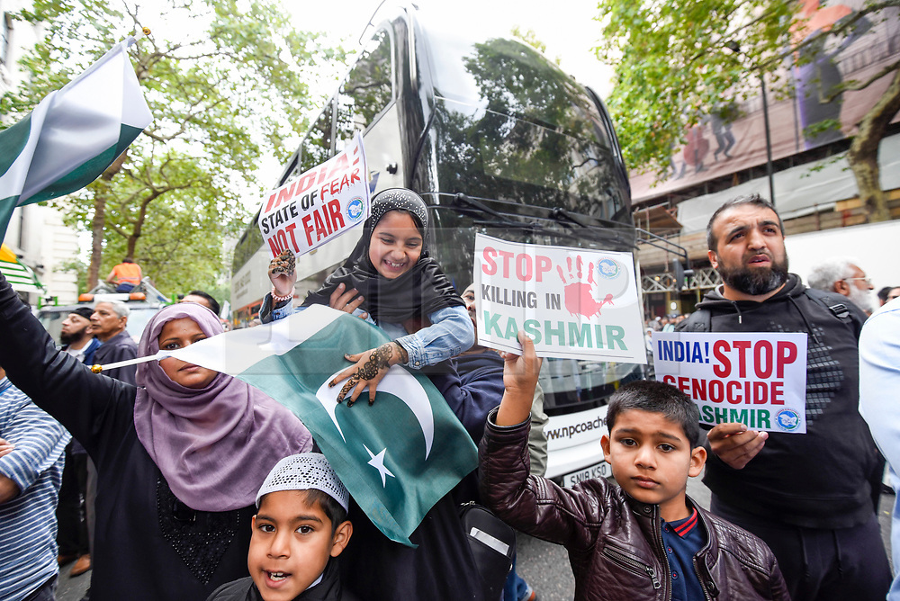© Licensed to London News Pictures. 15/08/2019. LONDON, UK.  A family joins thousands of protesters, many waving Pakistani and Kashmiri flags, outside the Indian High Commission in Aldwych, on what they are calling Black Day, to stand in solidarity with the people of Kashmir.  Indian Prime Minister Narendra Modi delivered an Independence Day speech highlighting his decision to remove the special rights of Kashmir as an autonomous region.  Photo credit: Stephen Chung/LNP