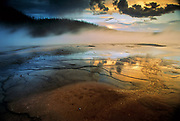 Sunset reflecting in Grand Prismatic Spring, one of the famous geysers in Yellowstone National Park