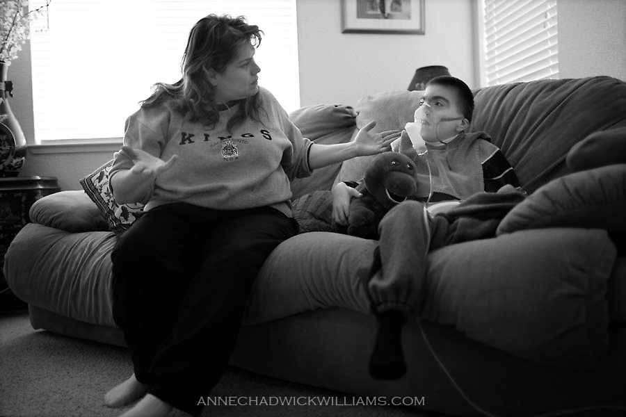 Melissa Kinley gestures to her disabled son, Kevin, 17, while she runs a ventilator on him to clear up his breathing. She does this several times a day to keep is airway clear.